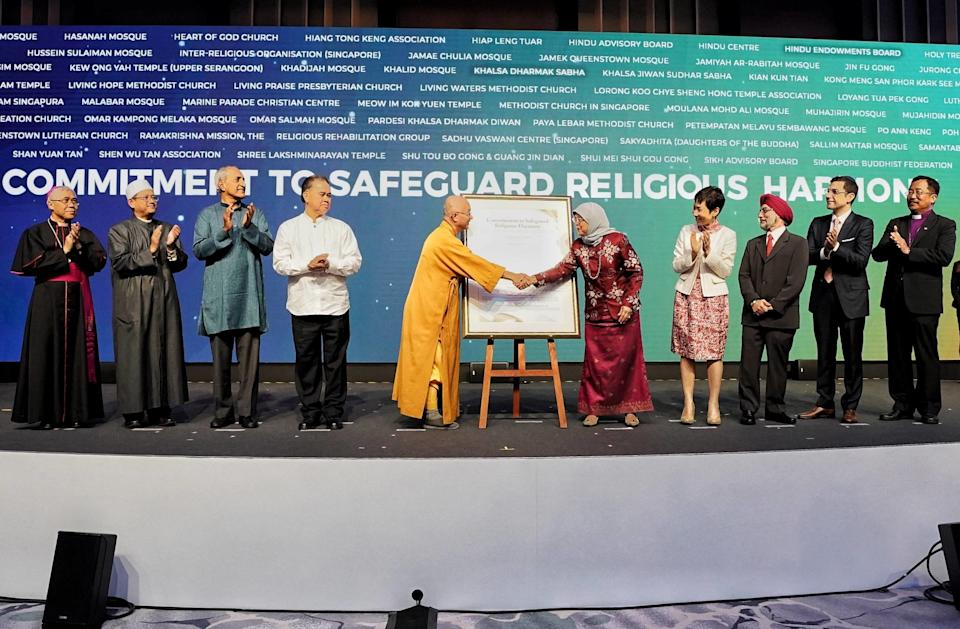 Senior religious leaders of Singapore present a framed copy of the commitment to safeguard religious harmony to President Halimah Yacob at the International Conference on Cohesive Societies at Raffles City Convention Centre on 19 June 2019. (PHOTO: International Conference on Cohesive Societies)