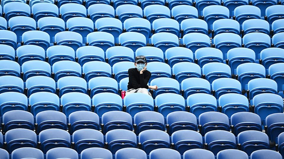A spectator, pictured here wearing a mask in Rod Laver Arena.