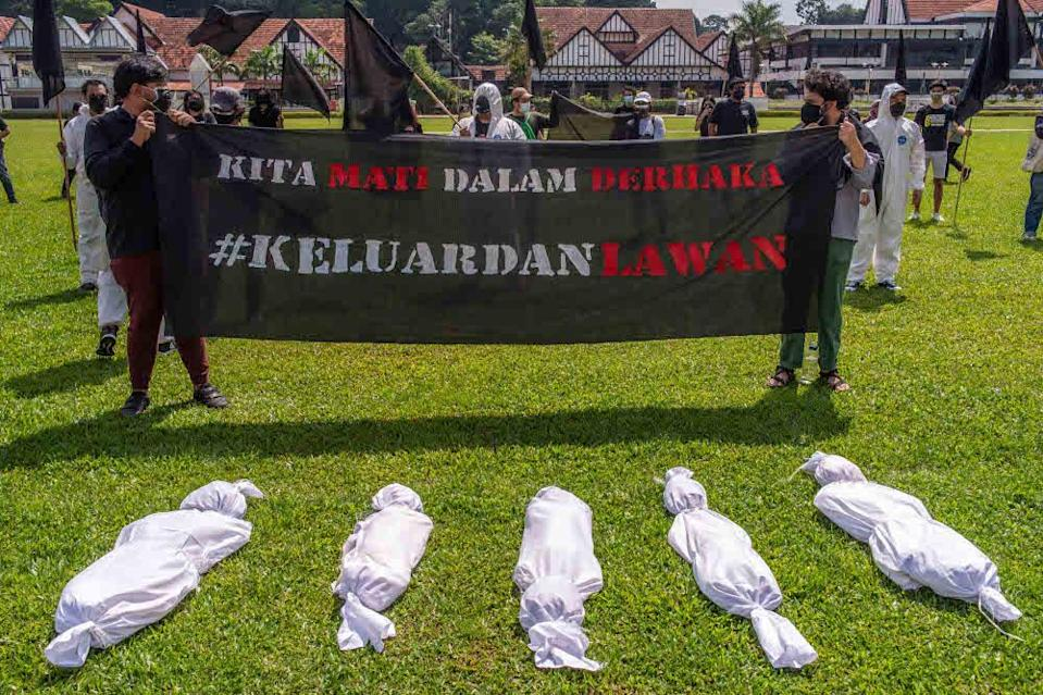 Protesters wearing personal protective equipment (PPE) holding banners and effigies of corpses during the Black Flag protest demanding the resignation of prime minister Tan Sri Muhyiddin Yassin. — Picture by Shafwan Zaidon
