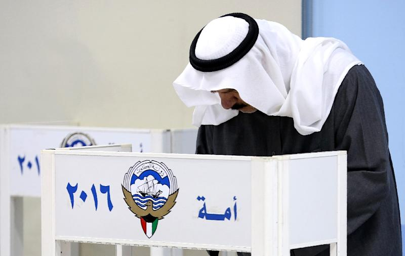 A Kuwaiti man writes on his ballot paper before casting his vote for the parliamentary elections at a polling station in Kuwait City on November 26, 2016 (AFP Photo/Yasser Al-Zayyat)