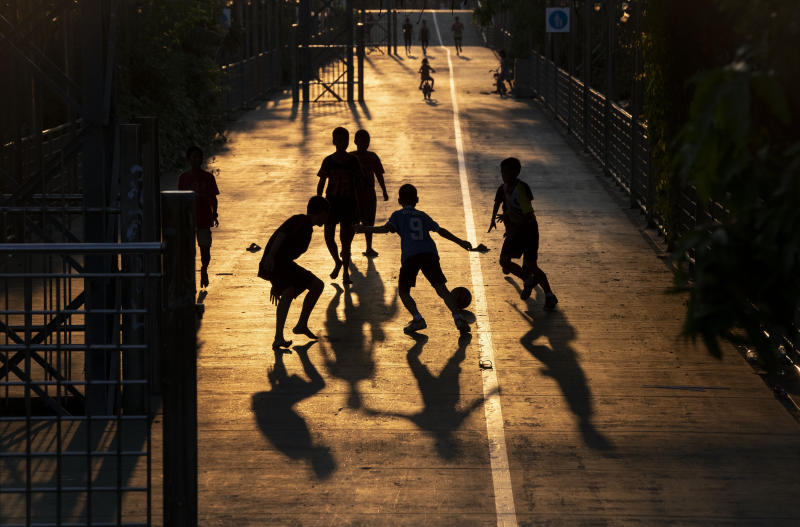 Children play soccer in the afternoon light in Bangkok, Thailand, Wednesday, March 25, 2020. Thailand's government announced a state of emergency to start on Thursday, March 26, 2020, to allow measures that might be needed to control the coronavirus outbreak that has infected hundreds of people in the Southeast Asian country. (AP Photo/Gemunu Amarasinghe)