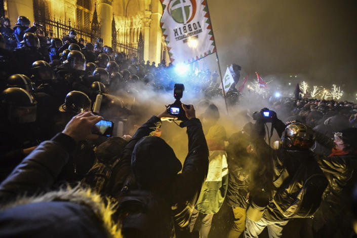 """Protesters clash with police during a demonstration against the amendments to the labour code, dubbed """"slave law"""" by oppositional forces, at the parliament building in Budapest, Hungary, Dec. 13, 2018. The rally, which was announced by the Free University and Students Trade Union student groups, started peacefully but police later responded to aggressive protestors with teargas. (Marton Monus/MTI via AP)"""