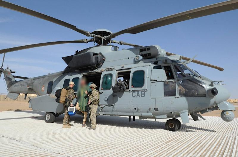 Two soldiers of the French special forces standing next to Dutch national Sjaak Rijke (C) as he gets off of a Caracal Helicopter after being released, at a French Military airbase in Mali (AFP Photo/-)