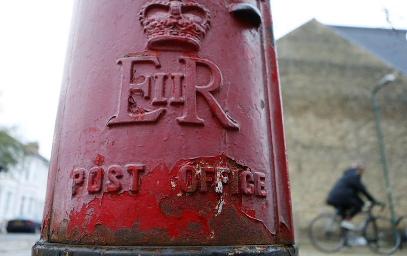 A man rides a bicycle past a postbox in London