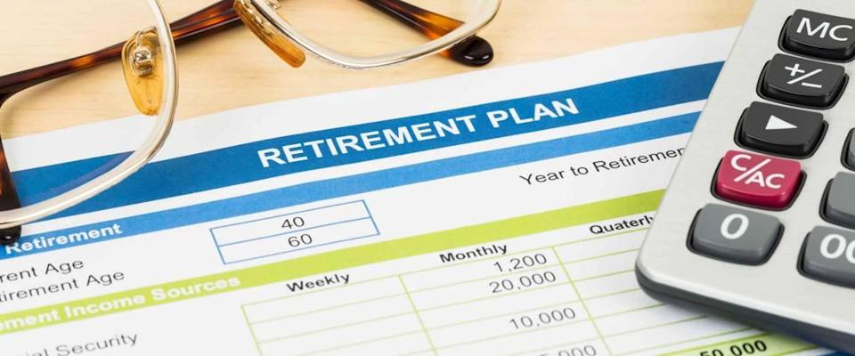 Retirement plan print out with glasses and calculator.