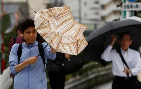 Passersby using umbrellas struggle against a heavy rain and wind wind caused by Typhoon Faxai in Tokyo