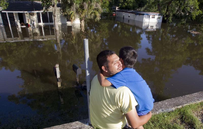Jorge Torrez hugs his son Jayden, 12, as they sit on a wall overlooking their flooded home in Live Oak Fla., Wednesday, June 27, 2012. Dozens of homes and much of the downtown area was flooded by torrential rains from Tropical Storm Debby. (AP Photo/Dave Martin)