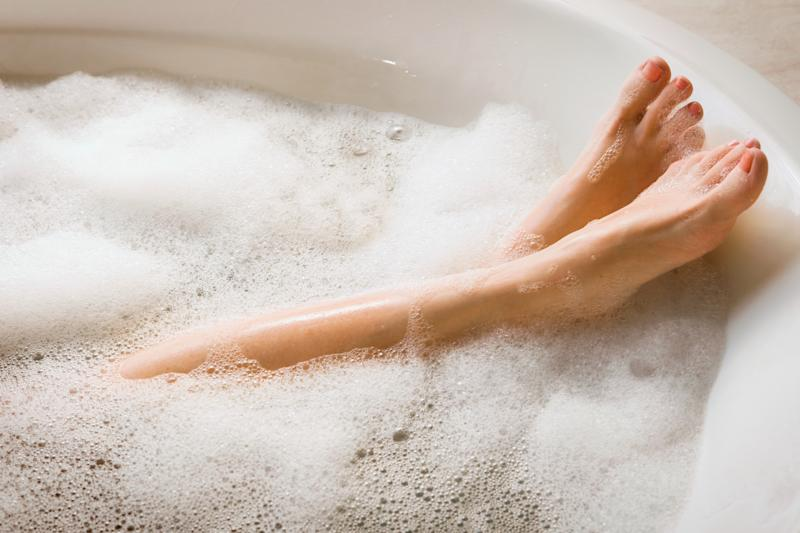 A person crosses her leg in the bath tub