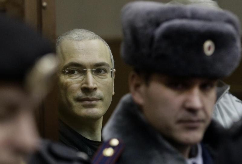 FILE In this Thursday, Dec. 30, 2010 file photo Mikhail Khodorkovsky, left, looks from behind glass at a court room in Moscow, Russia. Russian President Vladimir Putin said on Thursday Dec. 19, 2013, that he will pardon his arch-enemy Khodorkovsky who has spent the past 10 years in prison on tax evasion and embezzlement charges. Khodorkovsky's release could potentially be Putin's biggest political decision this year. (AP Photo/Ivan Sekretarev, File)
