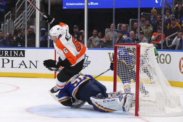 Philadelphia Flyers defenseman Travis Sanheim (6) trips over St. Louis Blues goalie Jordan Binnington (50) during the third period of an NHL hockey game Wednesday, Jan. 15, 2020 in St. Louis. (AP Photo/Dilip Vishwanat)