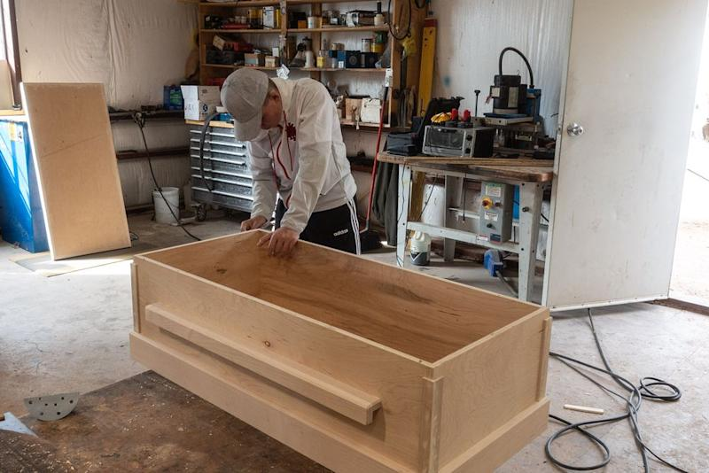 One of Rhonita Miller's nephews sands a coffin that was made for her by family members. | César Rodríguez—El País