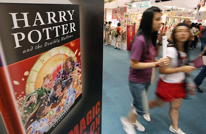 Two teenage girls walking past a Harry Potter book display at a book fair in China.