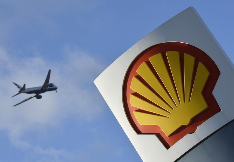 A passenger plane flies over a Shell logo at a petrol station in west London