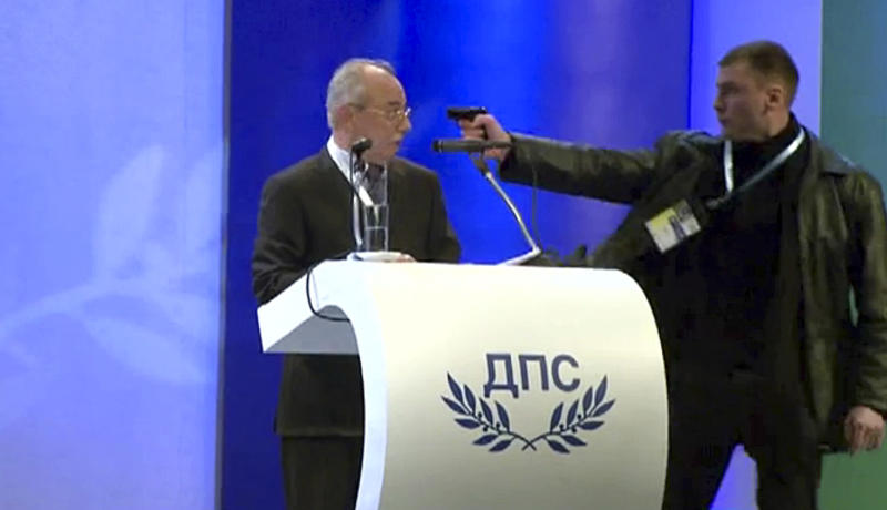 FILE - This is a Saturday Jan. 19, 2013  file image taken from video  shows a man identified as Oktay Enimehmedov, 25, as he points a weapon at Ahmed Dogan, left, leader of the Movement for Rights and Freedoms, during his speech at his party's congress in Sofia.  Enimehmedov who tried to shoot a gas pistol at the leader of his country's ethnic Turkish political party testified Tuesday Jan. 22, 2013 that his only regret is that his weapon didn't work. (AP Photo/ BTVnews, File)
