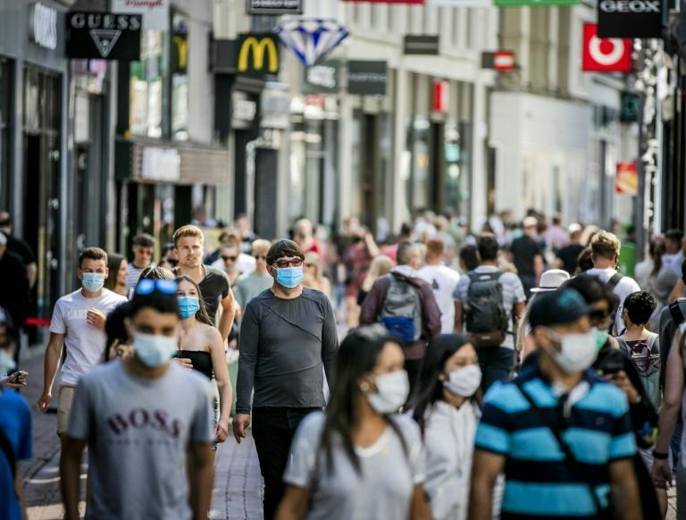People, wearing a face mask, walk in the Kalverstraat, in Amsterdam on August 5, 2020, from when wearing a face mask is mandatory in five usually crowded places in the city of Amsterdam (AFP Photo/Remko DE WAAL)