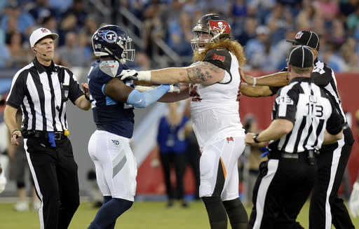 Officials break up Tennessee Titans linebacker Jayon Brown, left, and Tampa Bay Buccaneers offensive guard Ryan Jensen, right, in the first half of a preseason NFL football game Saturday, Aug. 18, 2018, in Nashville, Tenn. (AP Photo/Mark Zaleski)