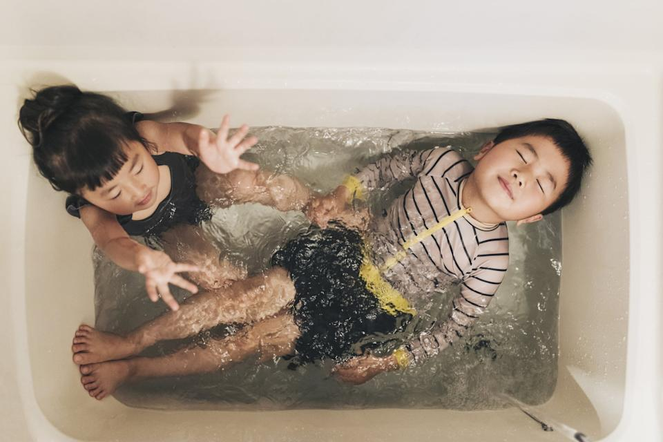 Asian brother and sister wearing swim wear and playing in the bathroom at home.