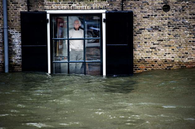 A Dutch local resident, standing in his house, looks to high waters level through his window, in Dordrecht on January 5, 2012. Gale force winds reaching up to 110 kilometres (about 70 miles) an hour as well as heavy rains are expected along the Dutch coast. About a quarter of the country sits below sea level.  AFP PHOTO / ANP / ROBIN UTRECHT  ***NETHERLANDS OUT - BELGIUM OUT***