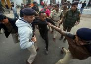 Policemen detain a demonstrator during a protest after India's parliament passed Citizenship Amendment Bill, in Agartala