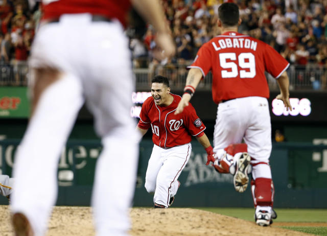 Washington Nationals' Wilson Ramos center celebrates with catcher Jose Lobaton, and others after Ramos hit the game winner during the ninth inning of a baseball game against the Pittsburgh Pirates at Nationals Park, Saturday, Aug. 16, 2014, in Washington. The Nationals won 4-3. (AP Photo/Alex Brandon)