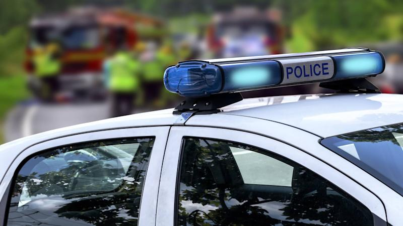 Police car with emergency services at car accident road scene