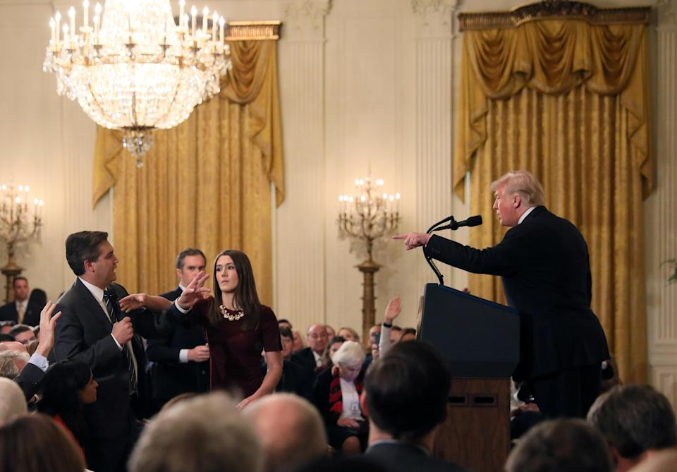 A White House staff member reaches for the microphone held by CNN's Jim Acosta as he questions President Trump during a 2018 news conference. (Jonathan Ernst/Reuters)