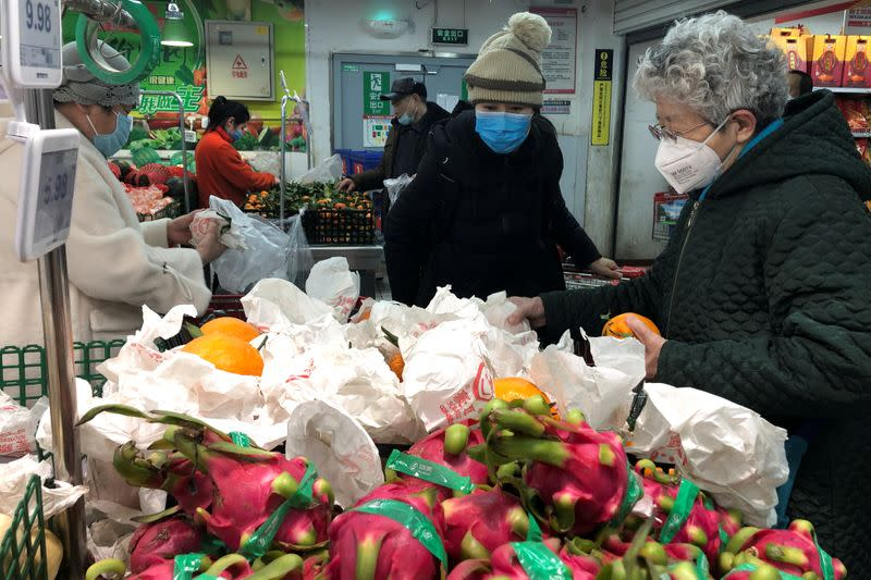 People wearing face masks select products at a supermarket, as the country is hit by an outbreak of the new coronavirus, in Beijing