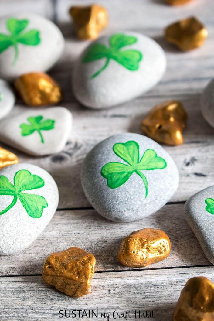 """<p>A perfect look for a tablescape, these painted rocks are also a great craft to do with your kiddos. </p><p><strong>Get the tutorial at <a href=""""https://sustainmycrafthabit.com/st-patricks-day-crafts/"""" rel=""""nofollow noopener"""" target=""""_blank"""" data-ylk=""""slk:Sustain My Craft Habit"""" class=""""link rapid-noclick-resp"""">Sustain My Craft Habit</a>.</strong></p><p><a class=""""link rapid-noclick-resp"""" href=""""https://www.amazon.com/s?k=gold+metallic+craft+paint&tag=syn-yahoo-20&ascsubtag=%5Bartid%7C2164.g.35012898%5Bsrc%7Cyahoo-us"""" rel=""""nofollow noopener"""" target=""""_blank"""" data-ylk=""""slk:SHOP GOLD METALLIC PAINT"""">SHOP GOLD METALLIC PAINT</a><br></p>"""
