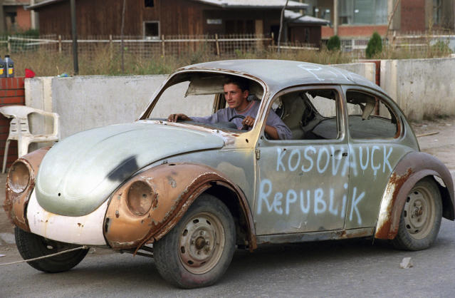 <p>An ethnic Albanian steers a decrepit car his family has salvaged as it is towed down a street in the provincial Kosovo capital, Pristina, on Sept. 21, 1999. (Photo: Jacqueline Larma/AP) </p>