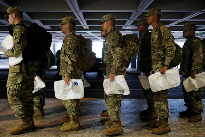 National Guard soldiers receive sterile coveralls to wear before checking the temperature of passengers arriving at Luis Munoz Marin International Airport, amid coronavirus (COVID-19) concerns, in San Juan, Puerto Rico, March 17, 2020. (Ricardo Arduengo/Reuters)