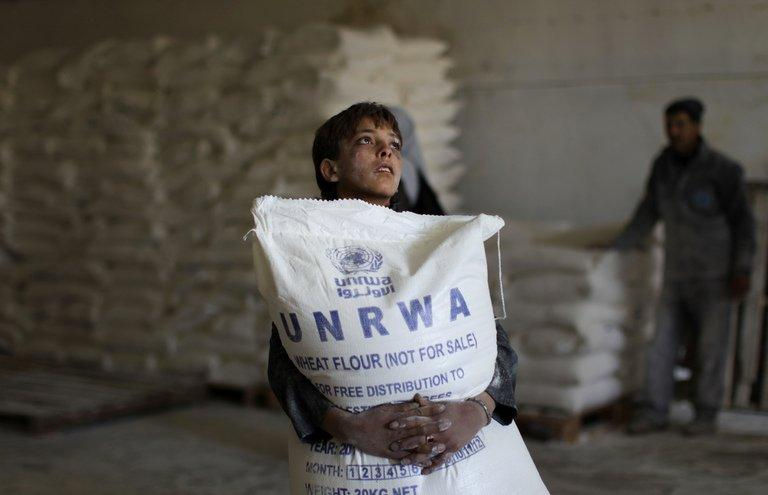 A Palestinian boy holds a sack of flour at a UNRWA aid distribution centre in Gaza City, on April 10, 2013