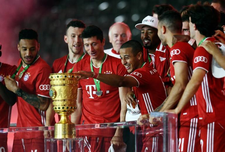 Thiago Alcantara touches the German Cup trophy after Bayern Munich's 4-2 triump over Bayer Levekursen in Saturday's German Cup final. (AFP Photo/ANNEGRET HILSE)