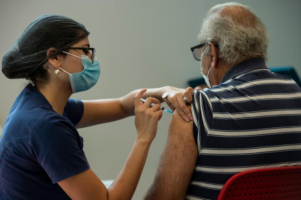 A healthcare worker gives a dose of the Coronavac vaccine to a man at a vaccination center in the Bicentenario Park, in Santiago, on February 10, 2021. - Chile surpassed one million people vaccinated against COVID-19 on February 9, 2021, six days after starting the mass immunization process in older adults, who joined the medical staff that has already been inoculated since December, the Ministry of Health reported. (Photo by Martin BERNETTI / AFP) (Photo by MARTIN BERNETTI/AFP via Getty Images)