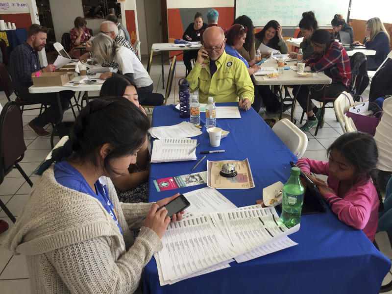 Pre-kindergarten teacher Shanel Rosetta, 23, of Albuquerque (left, foreground), makes calls to registered voters from a union hall in Santa Fe, N.M., on Tuesday, May 2, 2017, urging them to vote in favor of a tax on sugary sodas and other sweetened beverages. Voters in New Mexico's capital city were deciding whether to add a tax on sugary sodas and other sweetened beverages that would follow the examples of several cities across the country. The proposed tax in Santa Fe would pay to expand early childhood education. (AP Photo/Morgan Lee)