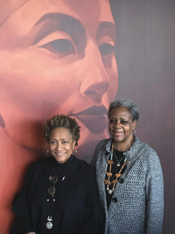 In this photo provided by Brad Fay, Beverly Mills, 71, left, of Pennington, N.J., and Elaine Buck, 67, of Hopewell Borough, N.J., stand in front of a mural in Princeton, N.J., on Jan. 19, 2019. The two have traced Black history in their local communities back the Revolutionary War and have founded a Black history museum nearby. They speak regularly on local Black history to schoolchildren and adult gatherings. (Brad Fay via AP)