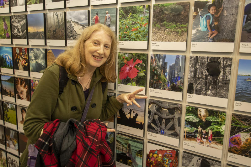 Photographer Amy of Queens, N.Y., gestures toward her photos selected to be in the exhibit. (Photo: Gordon Donovan/Yahoo News)