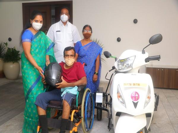 Kavitha handed over a handicapped scooter to Vinay in presence of his mother on Saturday. (Photo: ANI)