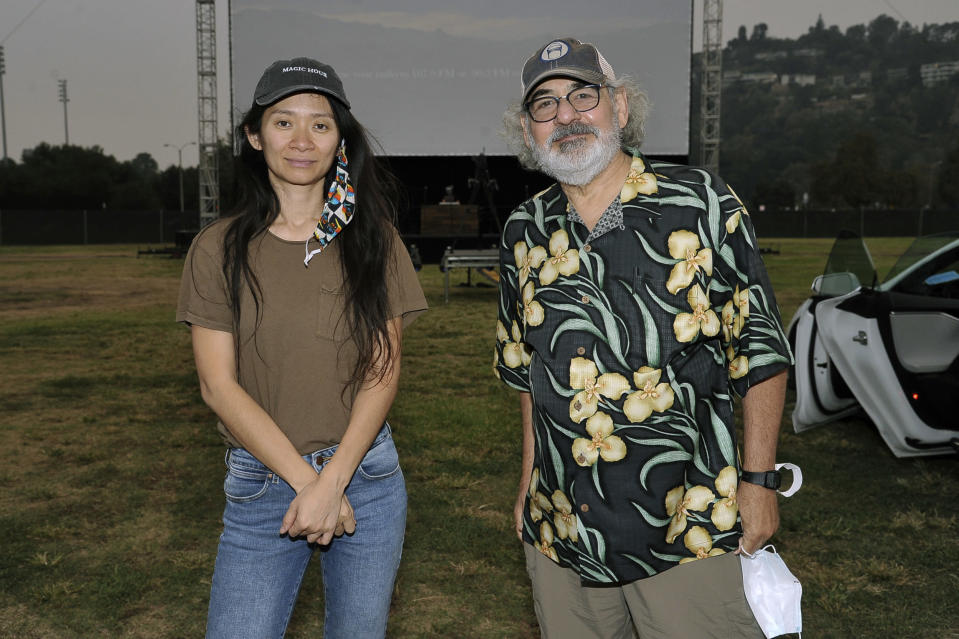 "Chloe Zhao, left, and Stephen Gilula attend the Telluride from Los Angeles drive-in screening of ""Nomadland"" on Friday, Sept. 11, 2020, at the Rose Bowl in Pasadena, Calif. (Richard Shotwell/Invision/AP)"