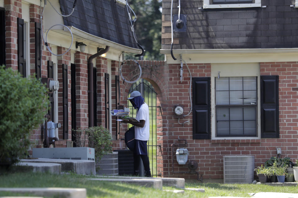 """A mail carrier delivers mail at a home at the Dutch Village apartments, Tuesday, July 30, 2019, in Baltimore. The apartment complex is owned by Jared Kushner, son-in-law of President Donald Trump, who days earlier vilified Congressman Elijah Cummings' majority-black Baltimore district as a """"disgusting, rat and rodent infested mess"""" where """"no human being would want to live."""" (AP Photo/Julio Cortez)"""
