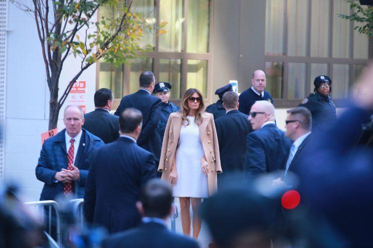 Melania Trump in a white dress with a camel coat casting her vote on election day.