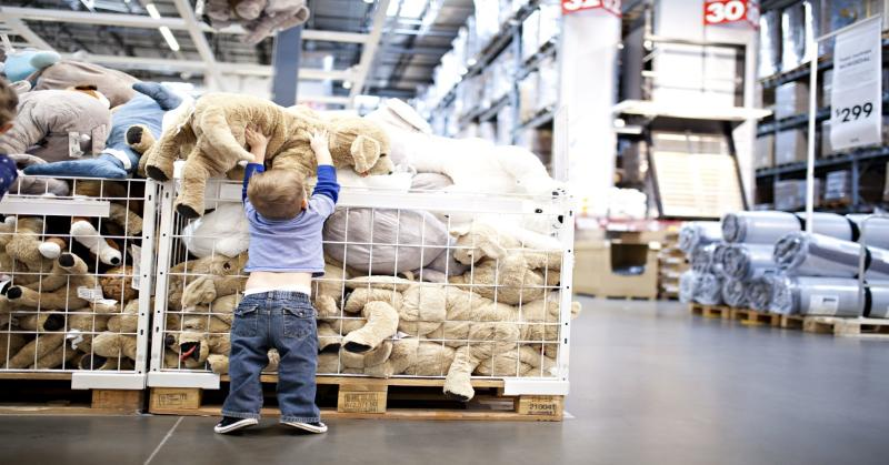 A child playing with a bin of stuffed animal toys at Ikea.