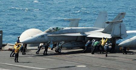 Sailors guide an F/A-18C Hornet assigned to the Valions of Strike Fighter Squadron (VFA) 15 on the flight deck of the aircraft carrier USS George H.W. Bush (CVN 77) in the Gulf, in this handout image taken and released on August 8, 2014. REUTERS/Mass Communication Specialist 3rd Class Lorelei Vander Griend/U.S. Navy/Handout via Reuters