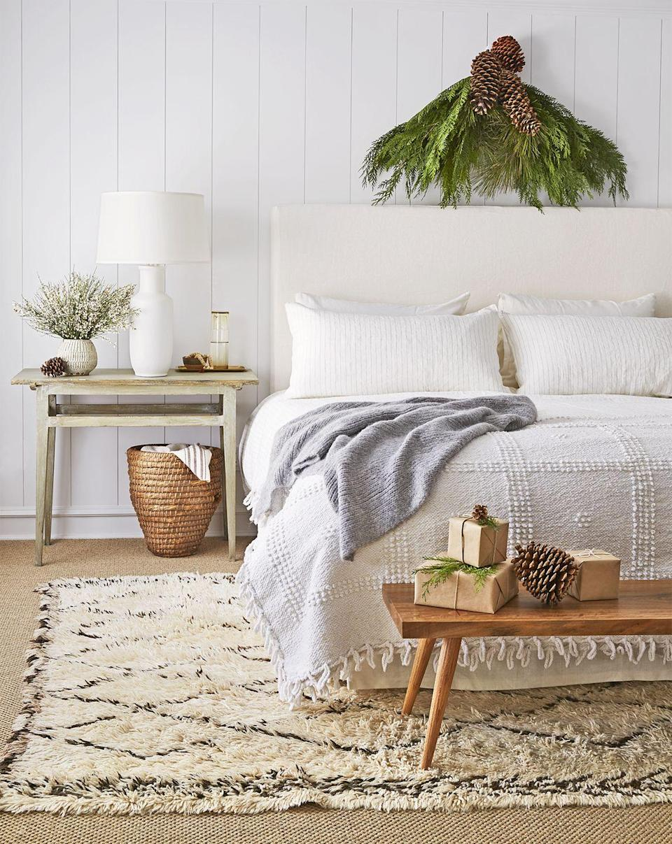 <p>Fringe and textured linens find a place in this understated bedroom. Incorporate darker colors by accessorizing with wicker baskets and wooden decor. </p>