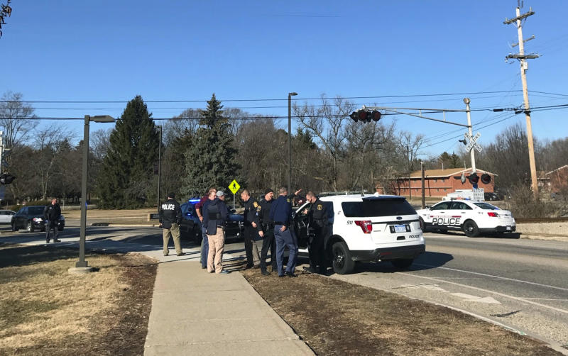 Authorities stand on the campus of Central Michigan University during a search for a suspect, in Mount Pleasant, Mich., Friday, March 2, 2018. School officials say police are responding to a report of shots fired at a residence hall at the university.
