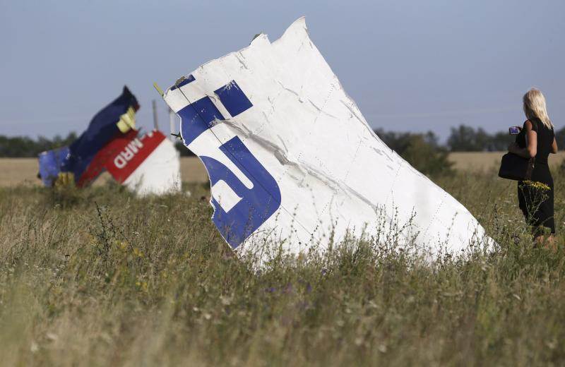 A woman takes a photograph of wreckage at the crash site of Malaysia Airlines Flight MH17 near the village of Hrabove (Grabovo), Donetsk region July 26, 2014. Nearly 300 people, 193 of them Dutch citizens, were killed when the Malaysia Airlines plane en route from Amsterdam to Kuala Lumpur was brought down in eastern Ukraine, where separatists are battling government forces, on July 17. REUTERS/Sergei Karpukhin (UKRAINE - Tags: POLITICS DISASTER TRANSPORT CIVIL UNREST TPX IMAGES OF THE DAY)