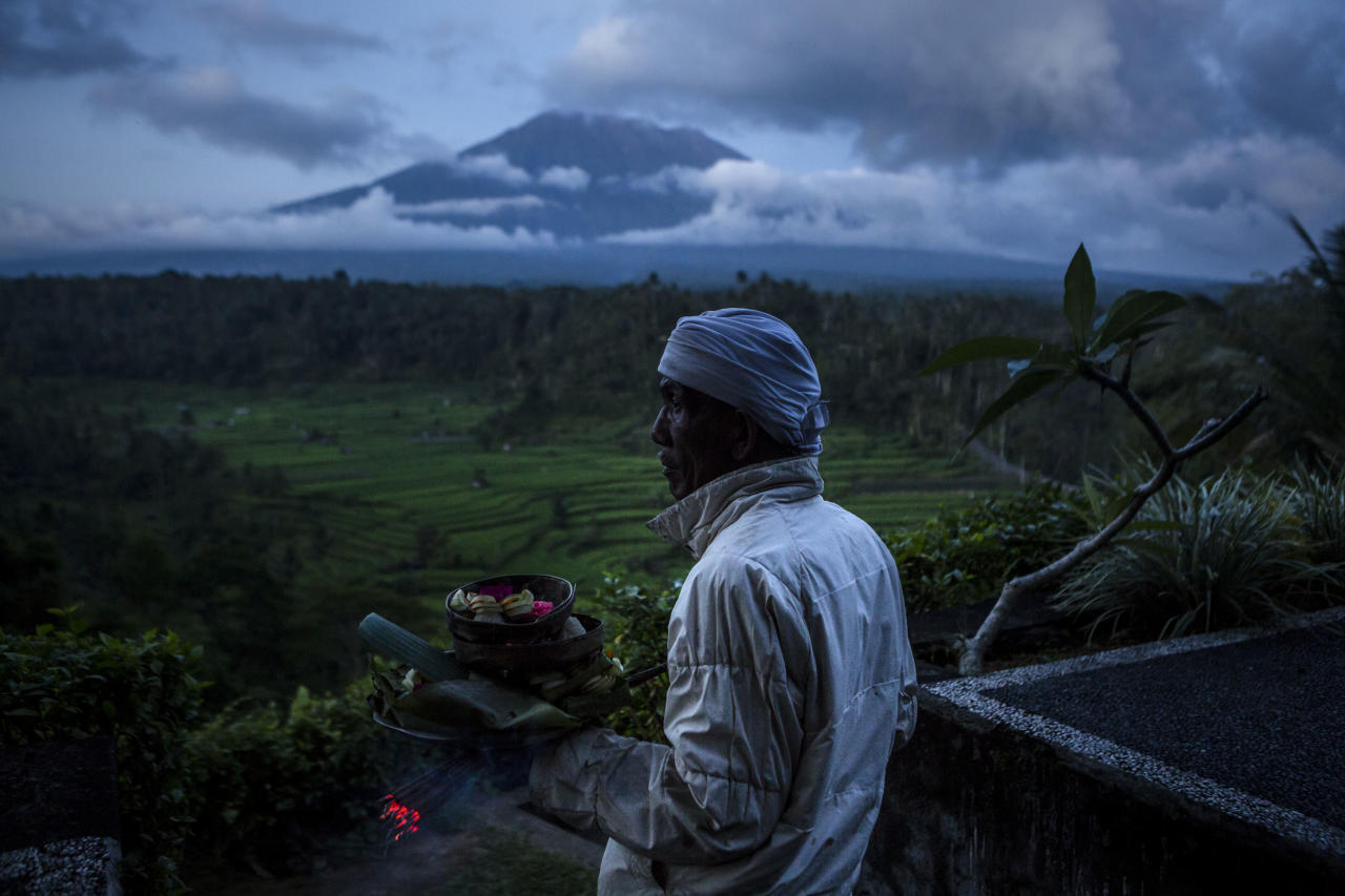 <p>A Balinese man prepares for pray with Mount Agung in the background. Indonesian authorities declared a state of emergency as hundreds of tremors were recorded at Bali's Mount Agung volcano and around 130,000 villagers evacuated their homes. (Ulet Ifansasti/Getty Images) </p>
