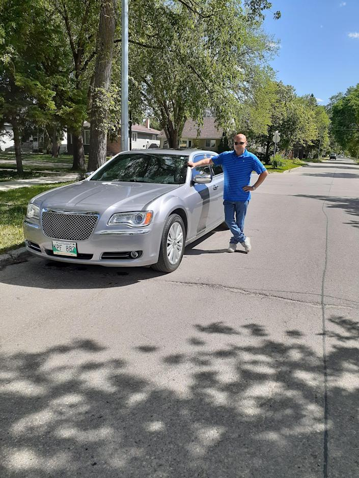 Stewart Westlake of Manitoba, Canada, poses with his Chrysler 300, a vehicle outfitted with a V6 engine.