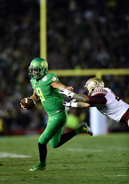 Jan 1, 2015; Pasadena, CA, USA; Oregon Ducks quarterback Marcus Mariota (8) rushes for a touchdown during the second half of the 2015 Rose Bowl college football game against the Florida State Seminoles at Rose Bowl. (Robert Hanashiro-USA TODAY Sports)