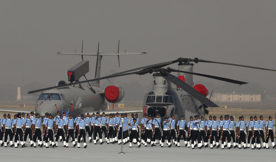 Indian Air Force personnel march past Chinnook helicopter, right, and a multi-sensor airborne early warning and control (AEW&C) system on a carrier jet during Air Force Day parade at Hindon Air Force Station on the outskirts of New Delhi, India, Thursday, Oct. 8, 2020. (AP Photo/Manish Swarup)