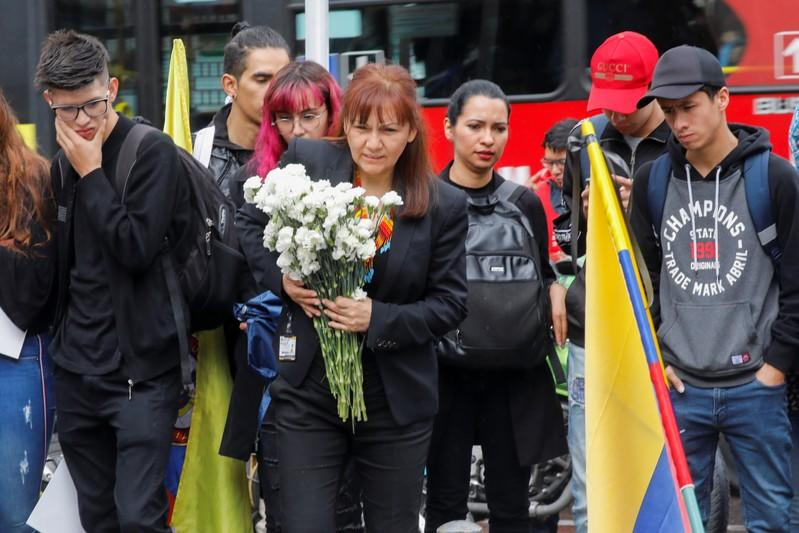 A person holds flowers during a gathering to honour Dilan Cruz, a teenage demonstrator who died after being injured by a tear gas canister during an initial strike last week, in Bogota